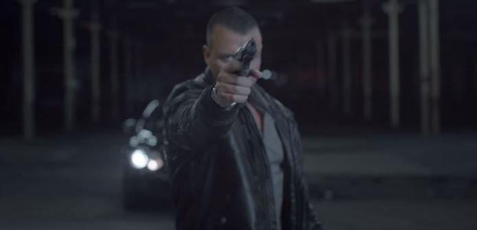 Kollegah mit erhobener Pistole im Musikvideo