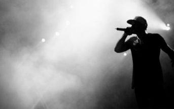 Silhouette eines Rappers der mit einem Mikro auf der Bühne steht