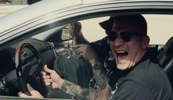Gzuz sitzt in seinem Auto mit Sonnenbrille und lacht verrückt