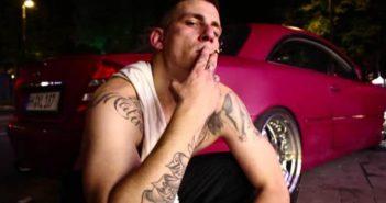 Gzuz sitzt vor seinem Mercedes Benz CL 500 und zieht an einer Zigarette