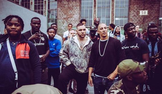 Farid Bang und Fler gemeinsam bei einem Videodreh von schwarzen Männern umgeben