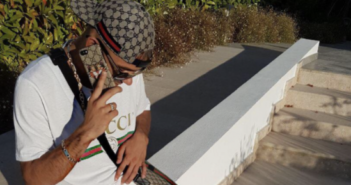 Capital Bra sitzt auf einem Stein und telefoniert mit seinem Smartphone
