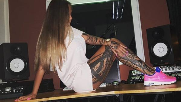 Schwesta Ewa auf dem Tisch mit nackten Beinen und Tattoos