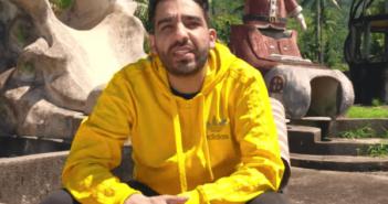 Fard sitzt vor einer Statue mit gelbem Hoodie